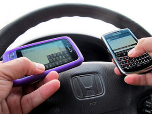 person holding two cell phones while at the steering wheel of a car, distracted driving, distracted driver, texting and driving, distracted driver awareness, united medevac solutions, ums, healthcare, healthcare staffing