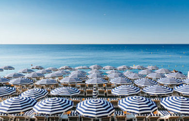 beach with a lot of chairs and umbrellas, summer tourists, summer, beach, summer tourism, summer vacations, healthcare, staffing, healthcare staffing, nursing, nurse staffing